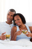 Intimate couple drinking a cup of tea on their bed Stock Photography