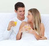 Intimate couple drinking orange juice on their bed stock photo
