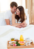 Intimate couple having breakfast lying in bed. At home Stock Images