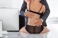 Intimate couple in office Royalty Free Stock Images