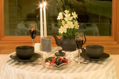 Intimate dining for two. Simple dinnerware dressed up with a tea pot full of flowers add a variety of candles and it becomes and elegant table setting for two Stock Image