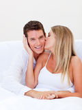 Intimate woman kissing her husband sitting on bed. At home Stock Photography