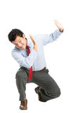 Intimidated Latino Office Worker Protecting Abuse. An intimidated latino man office worker in business attire crouching putting hands to shield in self defense royalty free stock images