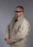 Intimidating bodyguard. Half body portrait of well built middle aged bodyguard wearing sunglasses, gray background Stock Images