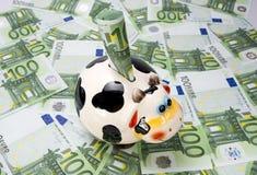 Intimorisca un salvadanaio su un campo verde di euro note Fotografie Stock Libere da Diritti