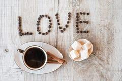 Intitule o amor dos grãos de café com copo e doces de café Fotografia de Stock