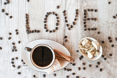 Intitule o amor dos grãos de café com copo e doces de café Fotografia de Stock Royalty Free