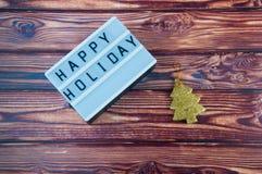 Intitule o pinheiro feliz do feriado e do ouro que coloca no fundo de madeira marrom Imagem de Stock Royalty Free