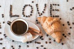 Intitulez l'amour des graines de café avec la tasse de café et le croissant Photographie stock libre de droits