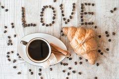 Intitulez l'amour des graines de café avec la tasse de café et le croissant Images stock