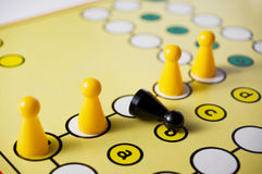 Intolerance in a Board Game. Symbolize by a black falling Figurine Royalty Free Stock Photo