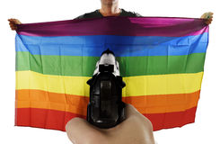 Intolerance violent representation of terrorist attack with hand pointing gun on proud gay holding flag Royalty Free Stock Photo