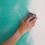 Intonacare la mano dell'uomo che insabbia il plaste nella cucitura del muro a secco Immagine Stock