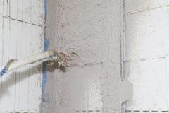Intonacare le pareti con uno spruzzatore intonacante della macchina e dello stucco della pompa Immagini Stock