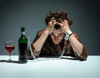 Intoxicated man sitting alone. Photo of youth addicted to alcohol, alcoholism concept, social problem Stock Images