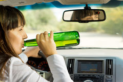 Intoxicated woman drinking and driving. As she swigs alcohol from the bottle while driving down the road Royalty Free Stock Photos