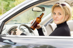 Intoxicated woman driver. Looking out of her side window with a serious expression as she drives by holding a bottle of booze in her hand Royalty Free Stock Image
