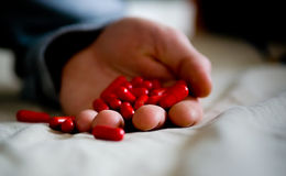 Intoxication. Holding a bunch of red capsules in the hand Stock Photography