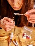 Intoxiqué de fille avec la cuillère et l'allumeur d'héroïne images stock