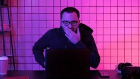 Intoxiqué masculin de jeu vidéo dans le capot jouant des tireurs pendant la nuit image stock