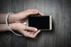 Intoxiqué mobile Mains attachées avec le fil Mains d'adolescent tenant le mobi photo libre de droits