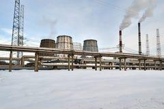 Intoxique a central térmica com tubulações de fumo em um fundo da paisagem do inverno Fotografia de Stock