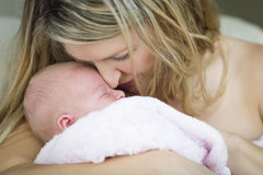 Intrattenere madre che tiene la sua ragazza di neonato preziosa Immagine Stock Libera da Diritti
