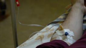Intraveneuze injectie Infusie van de drug in een ader door een IV Een mens in een het ziekenhuisafdeling ligt op een bed Hand stock footage