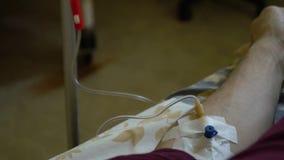 Intraveneuze injectie Infusie van de drug in een ader door een IV Een mens in een het ziekenhuisafdeling ligt op een bed Hand stock video