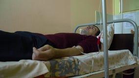 Intraveneuze injectie Infusie van de drug in een ader door een IV Een mens in een het ziekenhuisafdeling ligt op een bed stock video