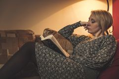 Intressant bok som en mogen kvinna läser arkivfoton