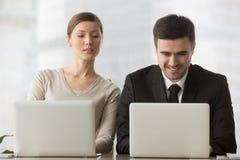 Intresserad nyfiken affärskvinna som ser affärsmanbärbar dator s arkivfoton
