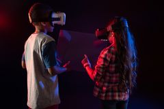 Intresserad pojke och en flicka som spelar VR-lekar arkivbilder