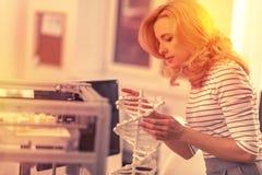 Intresserad smart dam som ser en modell av en DNAkedja arkivfoto