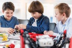 Intresserade barn som arbetar på tekniskt projekt Arkivfoto