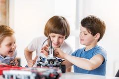Intresserade le barn som gör den tekniska leksaken Arkivbild
