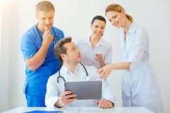Intresserade medicinska arbetare som störer deras kollega som använder minnestavladatoren royaltyfri foto
