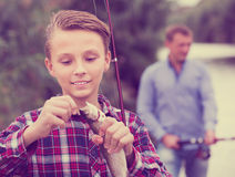 Intrested teenage boy releasing catch on hook fish Stock Photography