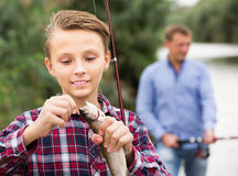 Intrested teenage boy releasing catch on hook fish Stock Photos