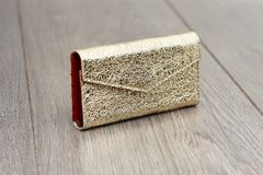 A goldy woman s clutch with cracks simmulated texture. An intresting woman s cluch made in golden and red colors with simmulated cracks on it s texture. It lays Royalty Free Stock Image