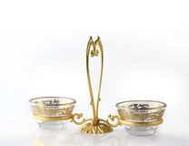 Intricate gilded glassware. Two intricate gold patterned glasses with a golden holder. Delicate design on white background Royalty Free Stock Photography