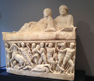 Intricate Roman marble frieze of battle scene. Sculpted battle scene of roman soldiers in white marble with reclining figures at their ease above Stock Photo