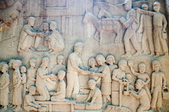 Intricate Thai carving mural -  Thai King activity help people Stock Image