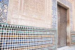 Intricate wall detail in the Alhambra Palace. In Granada, Andalusia, Spain showing relief stone carving, inlaid mosaics and decorative tiles around a doorway Stock Image