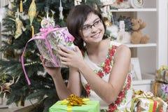 Intrigan a la muchacha al regalo de la Navidad Foto de archivo