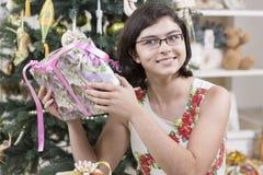 Intrigan a la muchacha al regalo de la Navidad Imagen de archivo libre de regalías