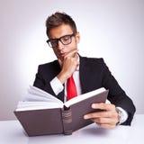 Intrigierter Geschäftsmann, der ein Buch liest Stockfotografie