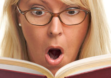 Intrigued Blonde Reads a Book Stock Photo