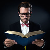 Intrigued businessman with glasses reading a book. Isolated on b Royalty Free Stock Image