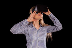 Intrigued woman in grey shirt wearing virtual reality 3D headset Stock Photos